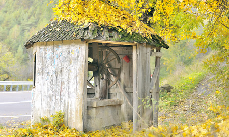 shingle: old fountain with shingle roof on autumn time, in Lepsa, Romania Stock Photo