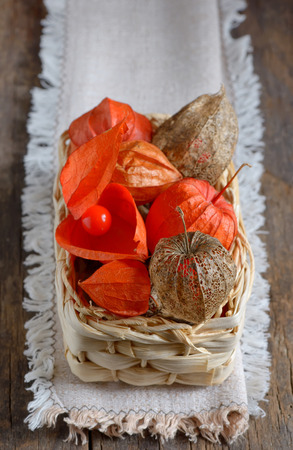 husk tomato: red Physalis fruits in straw basket, isolated on old wooden background