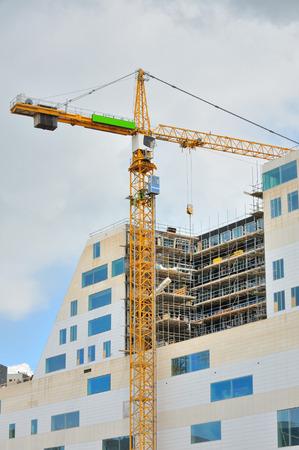 Trabajar grúa en un moderno edificio de oficinas en construcción Foto de archivo