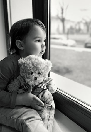 looking out: Little girl looking out the window at home