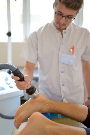tightness: Physiotherapist performs ultrasound physical therapy treatment