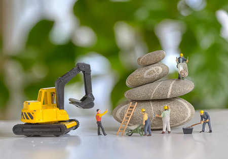 construction site: Pebbles stack and figurines of construction workers Stock Photo
