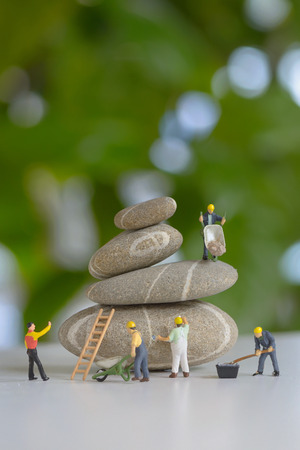 miniature: Pebbles stack and figurines of construction workers Stock Photo