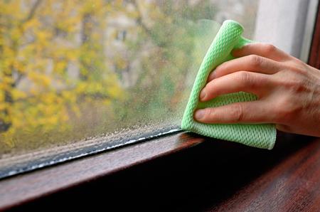 Žena čištění kondenzaci vody na okně