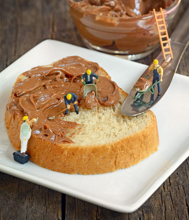 abstract food: minifigure workers  on bread and chocolate cream Stock Photo