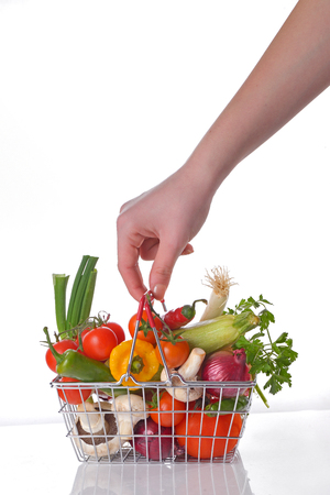 hand basket: Hand with wire shopping basket full of fresh vegetables