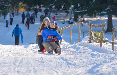 wintertime: teenagers slide downhill in wintertime