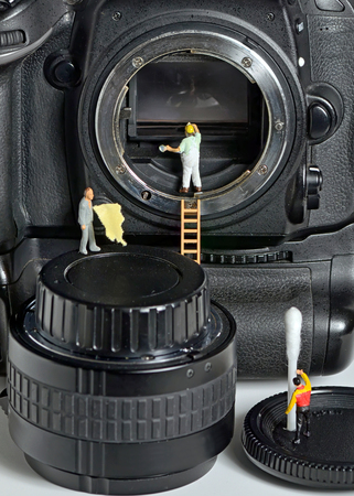 tiny lenses: Camera sensor cleaning by figurines Stock Photo