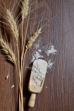 whole flour and wheat ears on wooden board