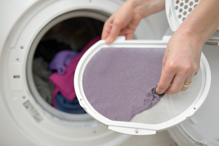 Woman Taking the lent of Dryer Machine