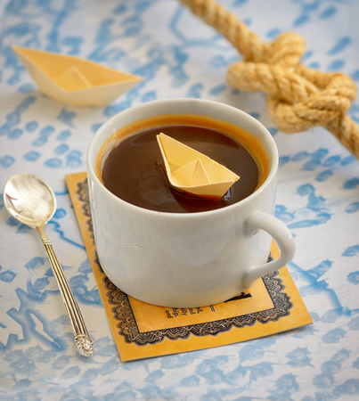 coffee cup and paper boat on map