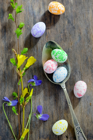 Easter wooden table setting with eggs and flowers