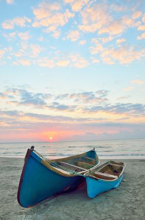 Blue boats on beach at sunrise