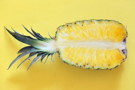 Raw cut pineapple on yellow surface table