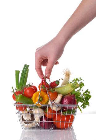 légumes crus et main dans le panier isolé sur blanc