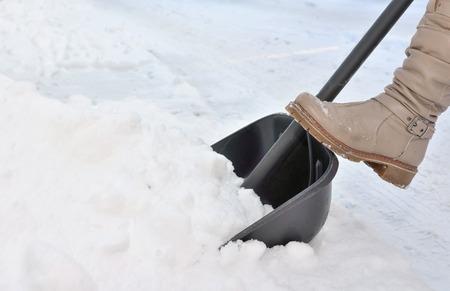 Woman Shoveling snow on street  in winter Stock Photo