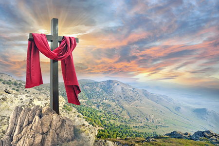 kruis met rode doek tegen de dramatische hemel Stockfoto