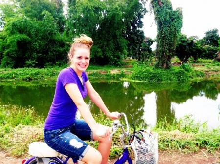 Girl rides bike in Thailand along a riverside  Banco de Imagens