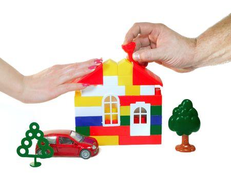 pull toy: Dos manos del hombre y la mujer (o la familia) se basa sue�os para construir la casa