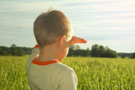space area: happy young boy looking horizon and dreaming on green field grass