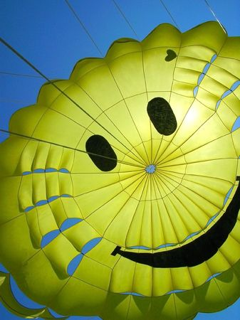 nylon: yellow fun parachute with smiling person