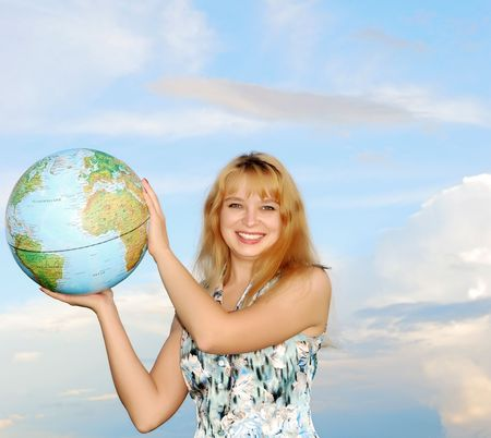 blonde in field on green grass holding globe in hand under blue sky(heaven) photo