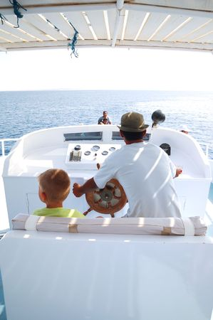 Young man and son on sailboat desk looks ahead photo