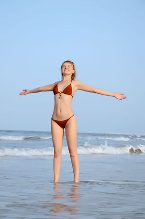 Happy girl on the beach against beautiful sky and sea. photo