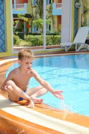 Young boy swimming in the indoor pool sitting Stock Photo - 5389328