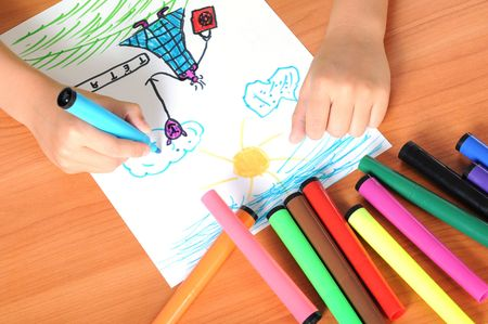 Caucasian boy drawing on paper with crayons