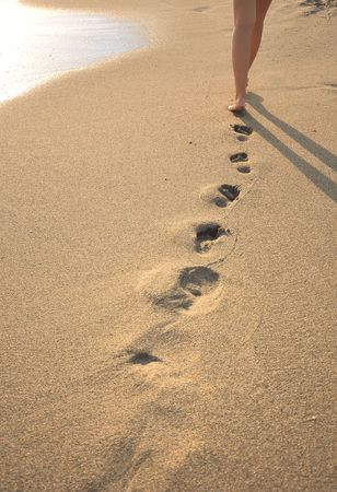 Human legs. Beautiful woman walking on the beach
