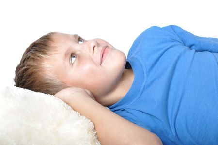 boy rests upon pillow, dreams and smiles Stock Photo