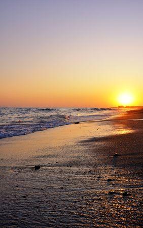 beautiful sunset on the beach with yellow bright sun photo