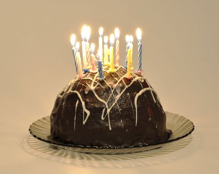 Chocolate cake with candles on a cake plate on a white background Stock Photo