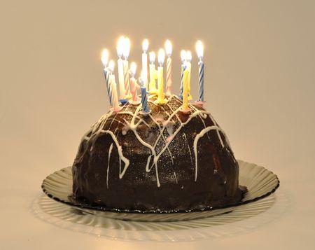Schokoladenkuchen mit Kerzen auf einem Kuchen-Teller auf weißem Hintergrund