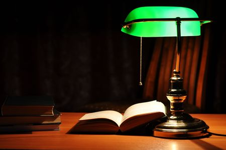 Electric green table lamp and opened book Stock Photo