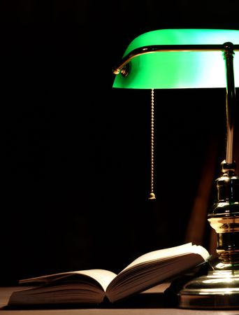 Electric green table lamp and opened book photo