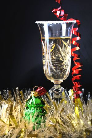 newyears: Glass of champagne and streamers. xmas decoration on black background