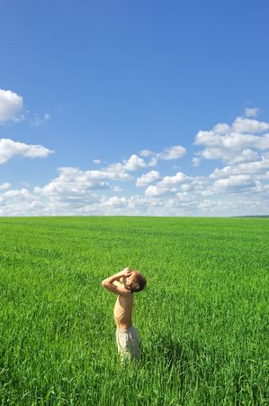 happy boy looking to the sun on green field, outdoor, nature scene