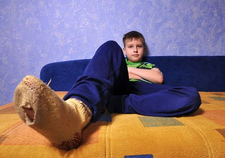 Boy wearing dirty socks with holes in them sits on sofa