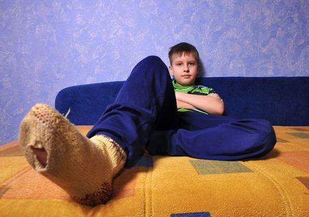 Junge tragen dirty Socken mit Löchern in ihnen sitzt auf sofa