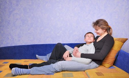 smiling woman and teen boy sits on sofa at home photo