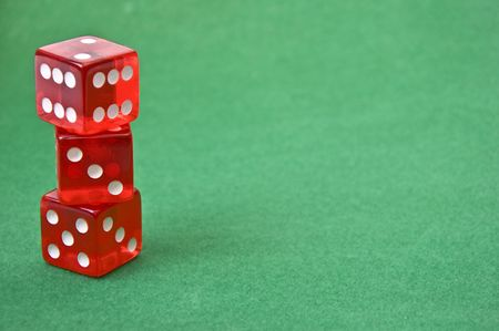set of three red dice against green baize Stock Photo