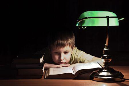 boy reads book in dark room under green lamp