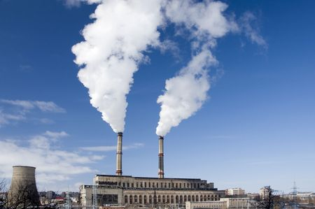 Power plant producing white smoke against a blue sky Stock Photo