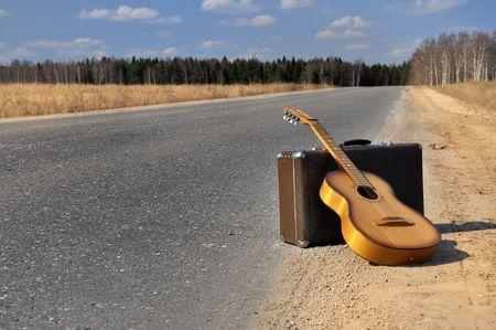 Gepäck und Gitarre liegt auf leere Landschaft-Straße