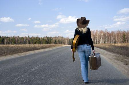 Country Girl mit Gitarre geht auf Straße Solitary unter Himmel