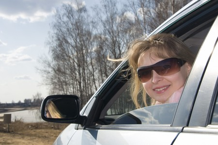 beautiful blond girl in sunglasses looking in the window of her car photo