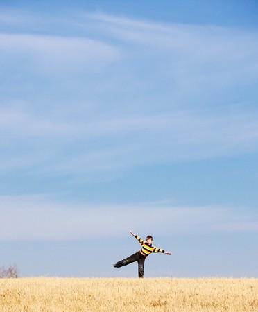 happy kid in wheat field under blue sky sunlight Stock Photo