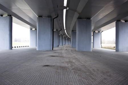 view on the road under concrete road bridge with column Stock Photo